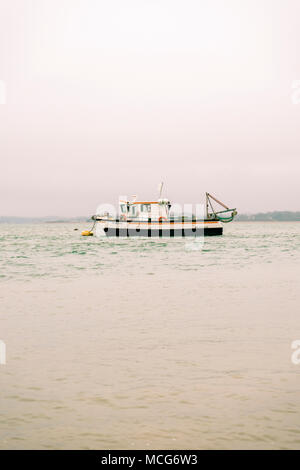 An empty fishing trawler/ fishing boat in the Solent near Calshot on a foggy overcast day, split toned, England, UK