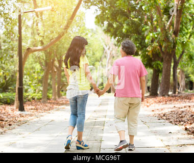 senior mother with daughter walking in the park - Stock Photo