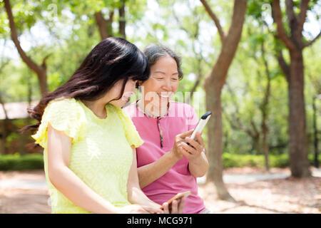 happy senior mother and daughterwatching the smart phone - Stock Photo