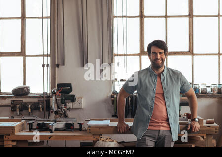 Portrait of a young woodworker smiling confidently while leaning against a workbench full of tools in his carpentry workshop - Stock Photo