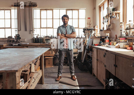 Portrait of a skilled young woodworker standing confidently with his arms crossed in his workshop full of carpentry tools - Stock Photo
