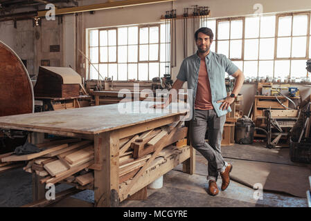 Portrait of a confident young woodworker standing next to a workbench full of wood in his carpentry workshop - Stock Photo