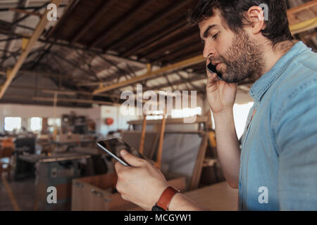 Young carpenter with a beard working alone in his large woodworking shop using a digital tablet and talking on a cellphone - Stock Photo