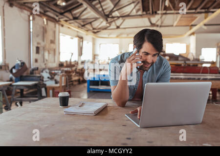 Smiling young craftsman standing at a workbench in his large workshop working online with a laptop and discussing designs with a customer on a cellpho - Stock Photo