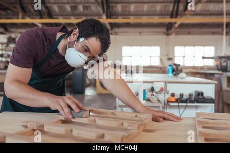 Skilled young woodworker wearing a protective mask and glasses hand sanding pieces of a wood while working alone in his large workshop - Stock Photo