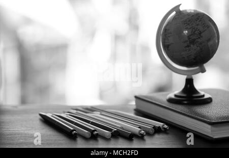 A pen on the desk with small globe - Stock Photo