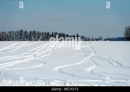 Drawings from snowmobile tracks on a snow-covered field in a winter day - Stock Photo