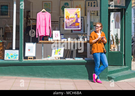 Woman holding mobile phone standing outside Tidy Print screen printing studio & shop at Gloucester Rd, North Laine, Brighton, East Sussex, England UK - Stock Photo