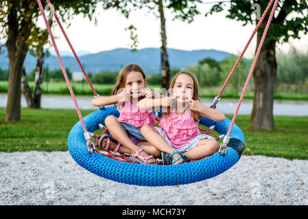 Identical twin girls on spider web nest swing on playground. Active Children playing with Giant Swing-N-Slide Monster Web Swing on outdoors playground - Stock Photo