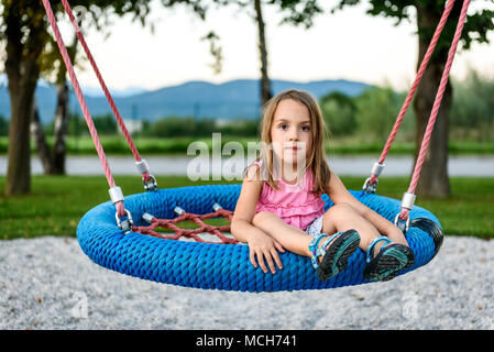 Little child girl on spider web nest swing on playground. Active Children playing with Giant Swing-N-Slide Monster Web Swing on outdoors playground in - Stock Photo
