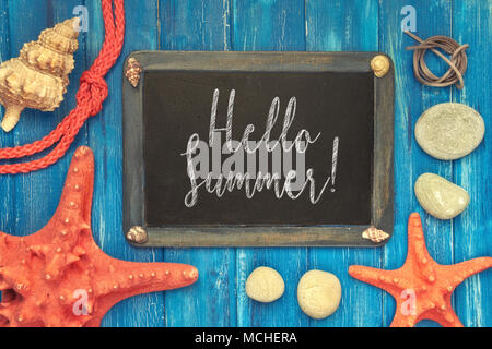 Blackboard with 'Hello Summer' chalk text, with sea shells, rope and star fish on blue  wooden background - Stock Photo