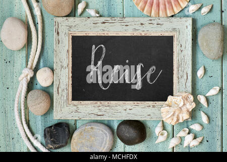 Blackboard With Maritime Decorations on light wood, text in German. 'Reise' means 'Vacations'. - Stock Photo