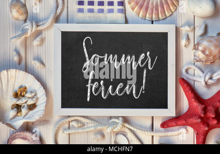 Blackboard With Maritime Decorations on light wood, text in German, 'Sommerferien' Means 'Summer Holidays' - Stock Photo
