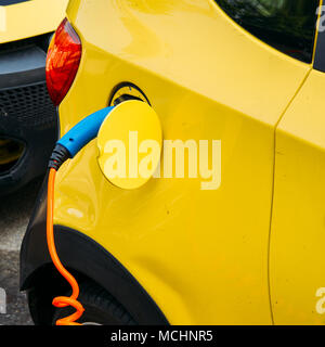 Close up of car being charged electronically at a public rechargeable dock station - Stock Photo