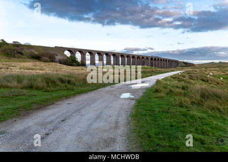 Near Ingleton, North Yorkshire, England, UK - September 11, 2016: A train passing the Ribblehead Viaduct on the Settle-Carlisle Railway - Stock Photo