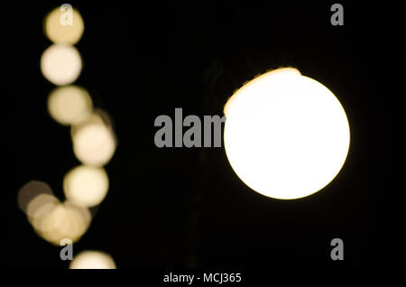 Soft bokeh background. Garland of electric lights. Place to add text. Blurry abstraction. Black & white. Dark night. Festive party in city. Soft focus - Stock Photo