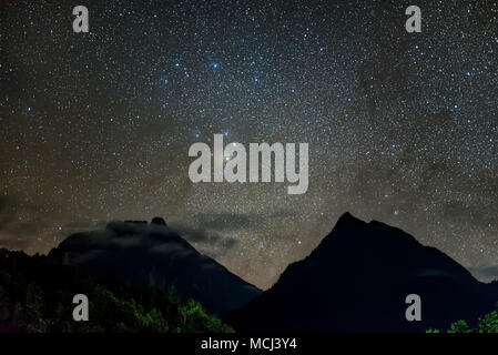 Antares rising in between Mt Kinabalu and Mt Nungkok. Long exposure and high ISO photograph with visible grain and noise, soft focus and motion blur - Stock Photo