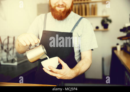 Coffee Business Concept - handsome bearded man in apron making coffee while standing at cafe - Stock Photo
