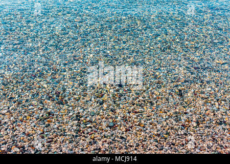 Background of blurred bright colorful sea stones under water. Iridescent sunlight on the stones. Transparent clear water of sea