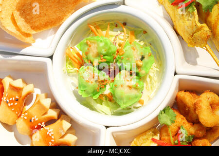 Close up mix delicious appitizer set: Dimsum ,sausace,chicken satay,calamari and rice cracker on white plate - Stock Photo