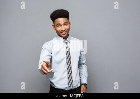 Business Concept - Happy handsome professional african american businessman giving name card to client. - Stock Photo