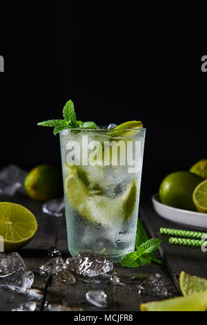 Mojito cocktail with lime and mint in highball glass with ice on a dark wood background with copy space at the top. - Stock Photo