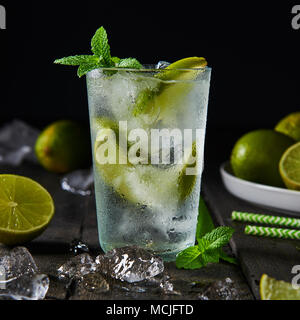 Mojito cocktail with lime and mint in highball glass with ice on a dark wood background. Square crop. - Stock Photo