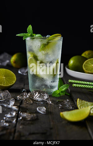 Mojito cocktail with lime and mint in highball glass with ice on a dark wood background with copy space. - Stock Photo