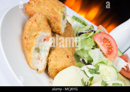 An English pub meal of deep fried breaded Chicken and vegetable rissoles with boiled potatoes and mixed salad - Stock Photo