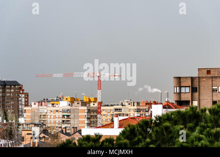Cityscape with construction crane against gray sky. - Stock Photo