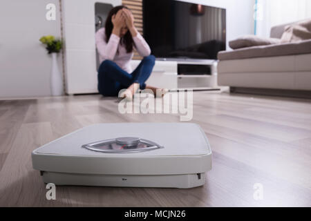 Close-up Of A Weighing Scale In Front Of Upset Woman - Stock Photo