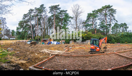 Orange Hitachi heavy plant mechanical digger in the foundations of a new house under construction on a building site in Surrey, southeast England, UK - Stock Photo