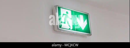 Emergency exit sign in a building glowing green - Stock Photo