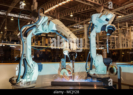 Industrial welding robots in production line manufacturer factory - Stock Photo