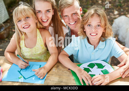 Happy family and kids paint eco recycle logo and home - Stock Photo