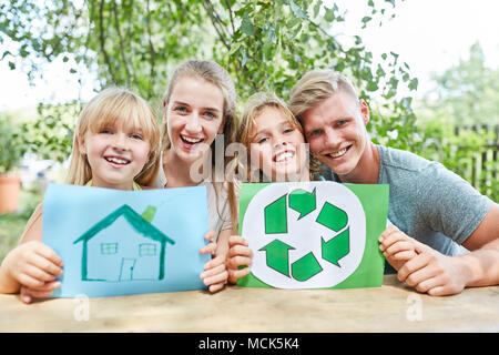 Happy family with drawing of home and recycle logo - Stock Photo