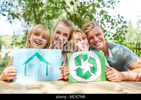 Happy family with drawing of dream house and recycle logo - Stock Photo