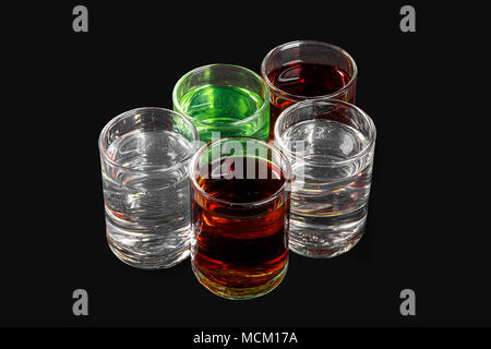 Multicolored transparent cocktails, a set of shots in a heap, a wedge, five servings. Side view from above Isolated black background. Drink for the me - Stock Photo