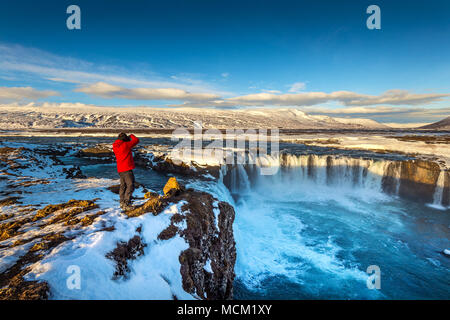 Photoghaper taking a photo at Godafoss waterfall in winter, Iceland. - Stock Photo