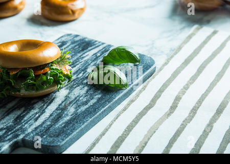 Salmon bagel on a stone cutting tablet with basil leaves on the side. - Stock Photo