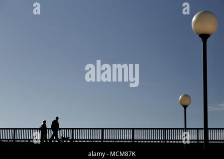 Silhouette of people walking across the bridge - Stock Photo