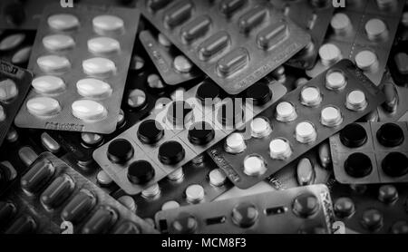 Full frame of pile of black and white photo of tablets pills in blister packs. Drug poisoning management concept. Heap of charcoal tablets and pills.  - Stock Photo