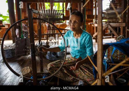 Senior woman weaving silk on spinning wheel inside house, Shan State, Myanmar - Stock Photo