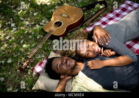 Couple lying in each others arms on a pinic blanket - Stock Photo