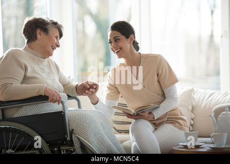 Senior in a wheelchair and beautiful nurse smiling and holding hands while reading a book - Stock Photo