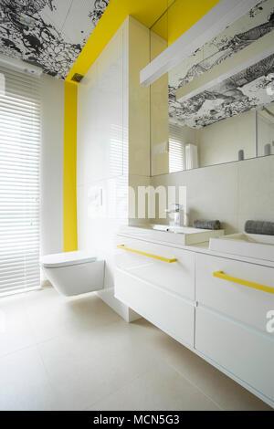 Trendy, modern, white bathroom interior design with creative yellow elements - Stock Photo