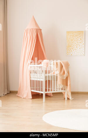 Pink canopy above white bed in pastel child's bedroom interior with gold painting on the wall - Stock Photo