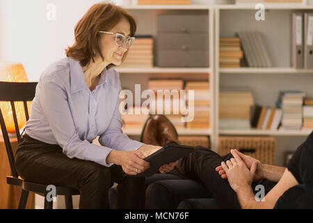 Elder therapist sitting in a chair and listening to a man in front of her - Stock Photo