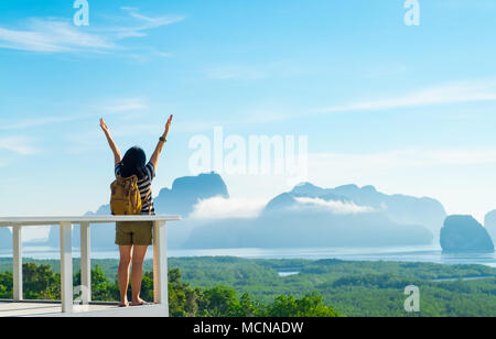 Happy young traveler woman backpacker raised arm up to sky enjoying a beautiful of nature at mountain panorama view point and sea,Freedom wanderlust,K - Stock Photo