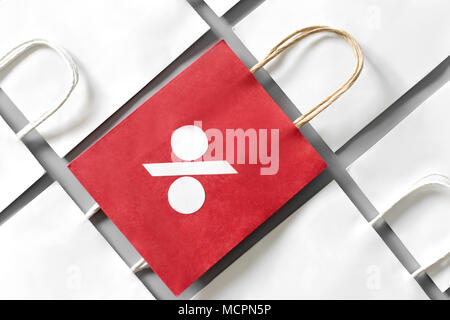 Red shopping bag from recycle paper with percent sign in a row of white shopping bags on gray background. Black friday or Christmas sales. - Stock Photo